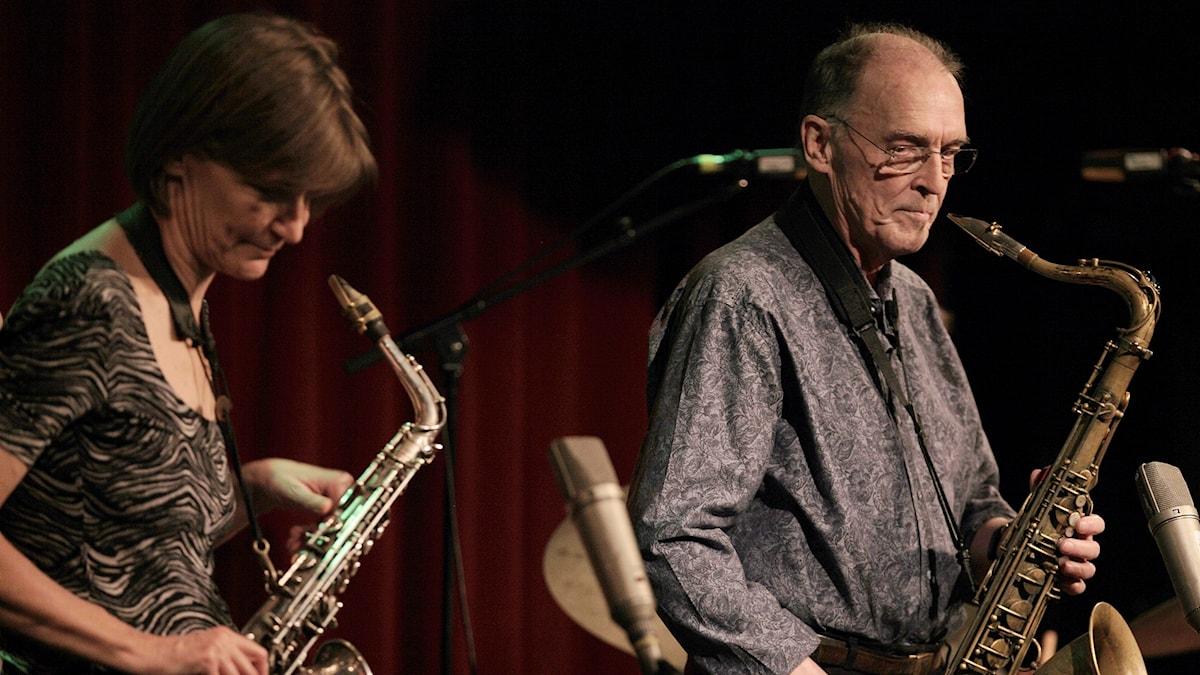 En kvinna och en man med varsin saxofon i händerna.