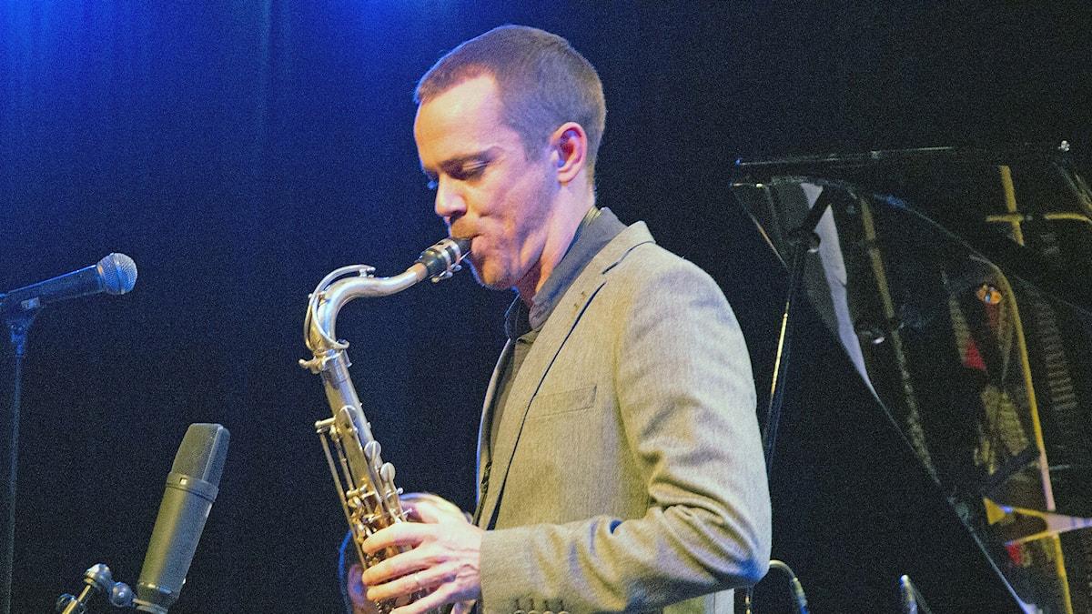 Saxofonist som spelar i sin tenorsax framför mikrofoner.