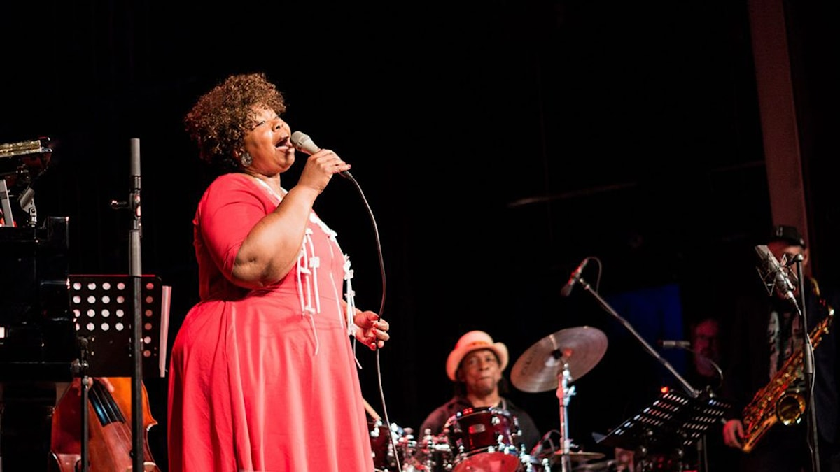 Sångerska i röd klänning som sjunger i mikrofon på en scen