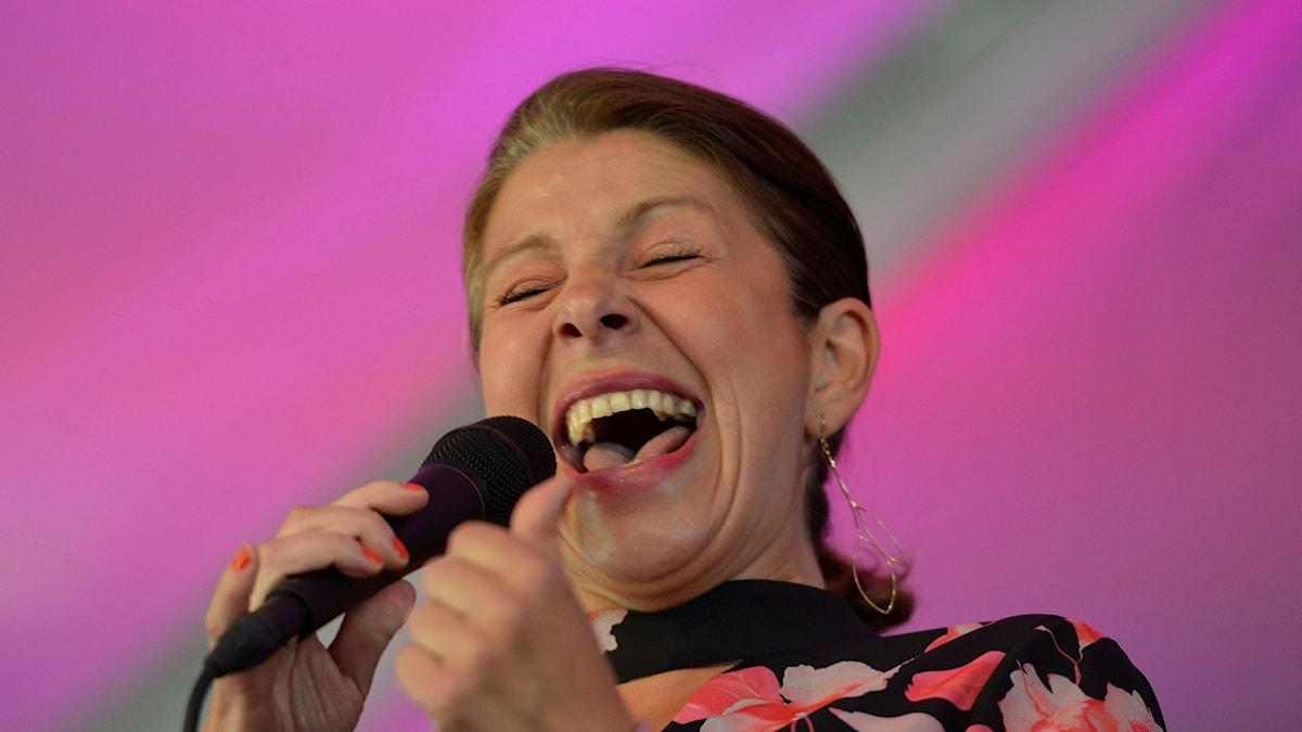 Kvinna som sjunger i mikrofon