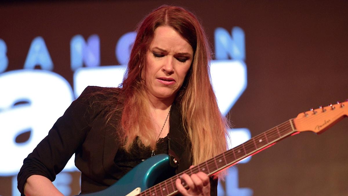 Kvinna som spelar gitarr