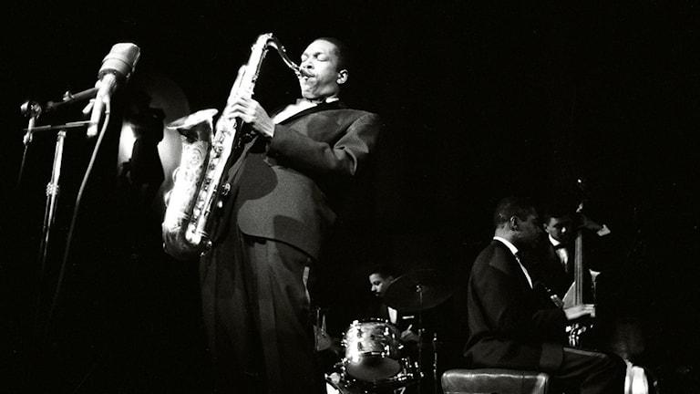 Saxofonisten John Coltrane med medmusiker i bakgrunden