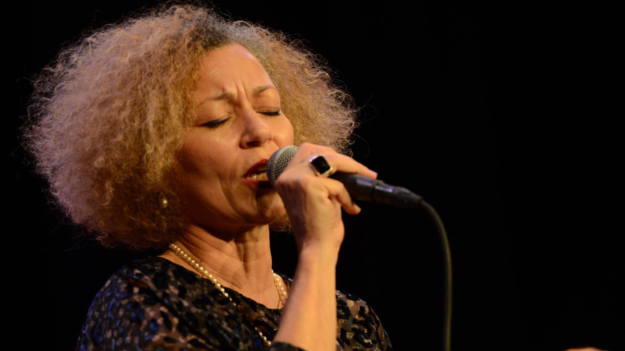 Sångerskan Rosàlia de Souza sjunger i en mikrofon.