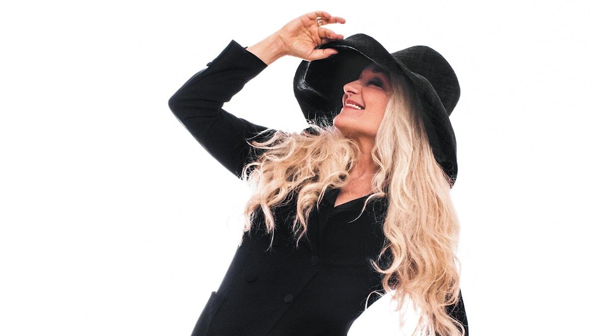 Kvinna med långt blont hår klädd i stor svart hatt