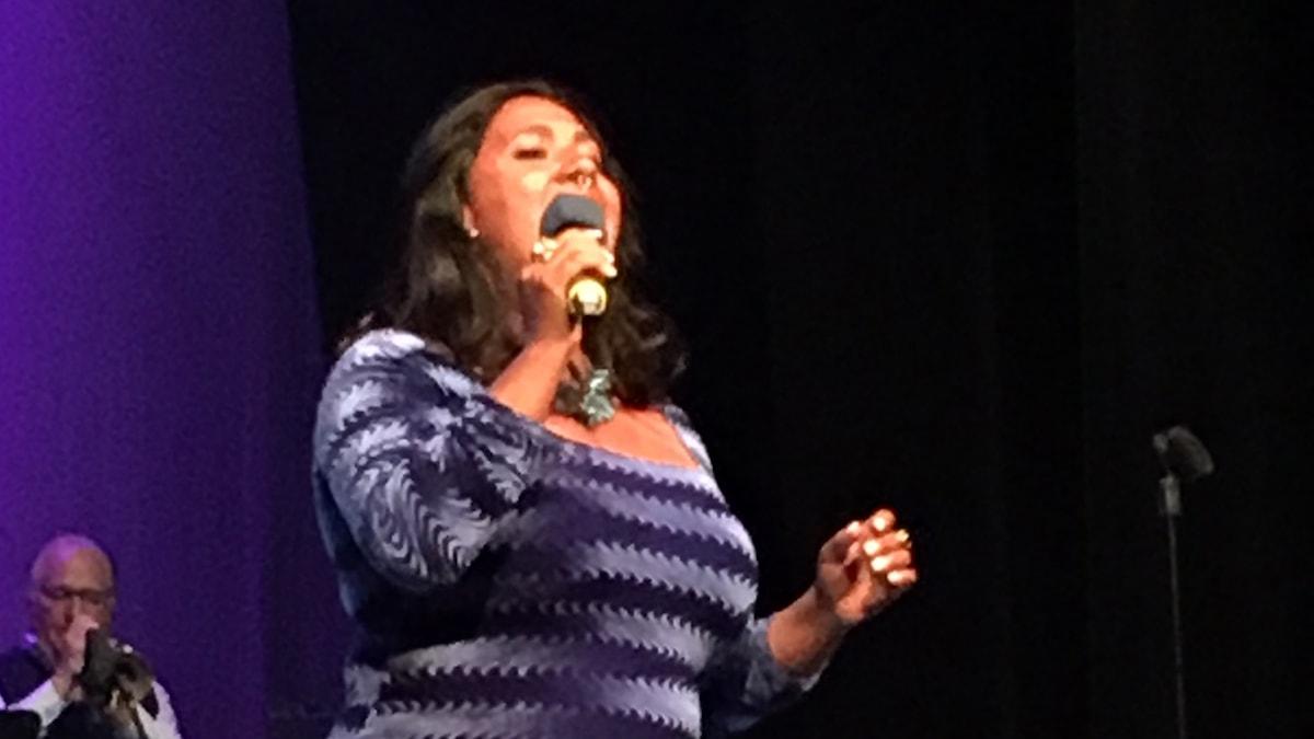 Sångerskan Kristin Amparo i en blå klänning, sjungades i mikrofon
