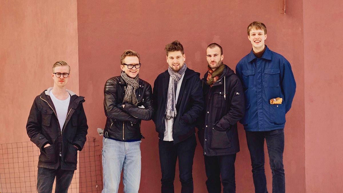 Fem unga män mot en rosa vägg i Oslo