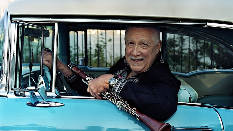 Klarinettisten Paquito D'Rivera med klarinetten i handen, tittar ut genom ett bilfönster