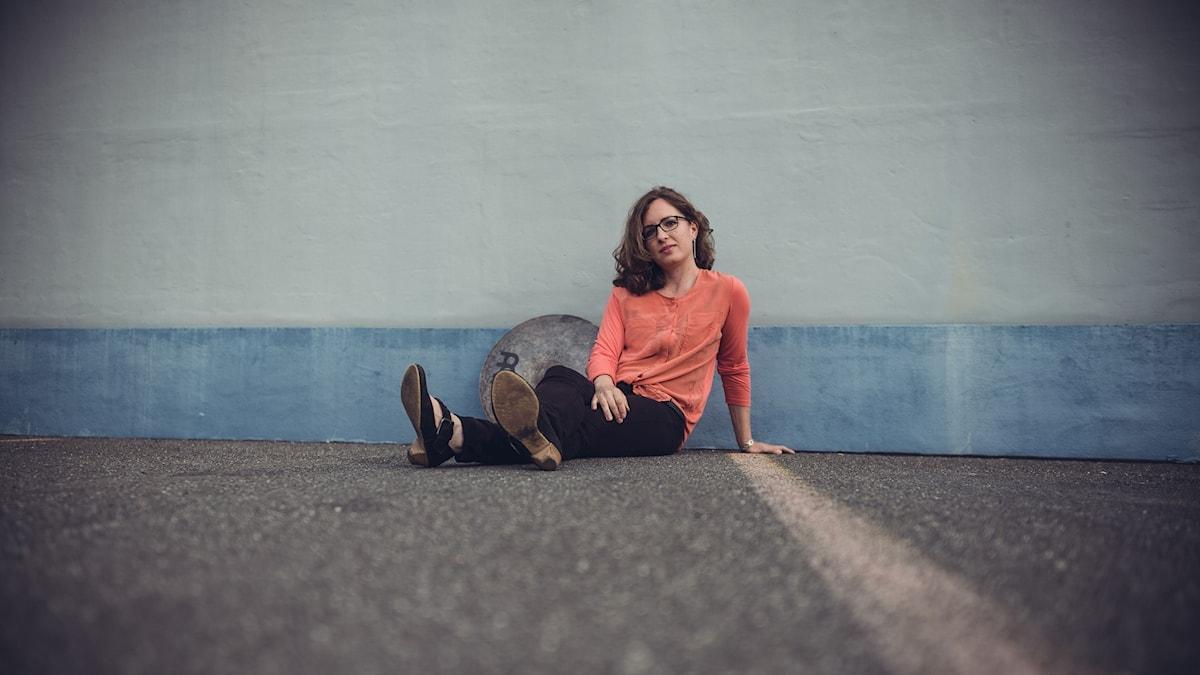 Ung kvinna som sitter på asfalten invid en betongvägg och med en cymbal bredvid sig.
