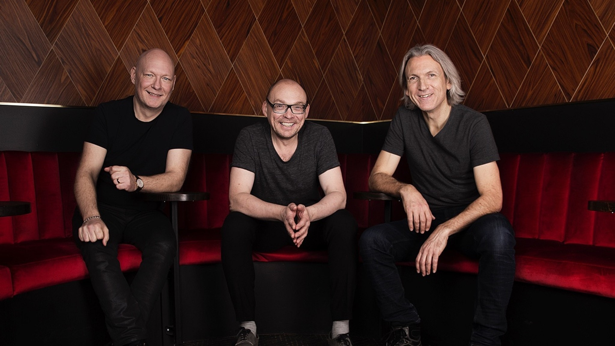 Tre glada män i en soffa