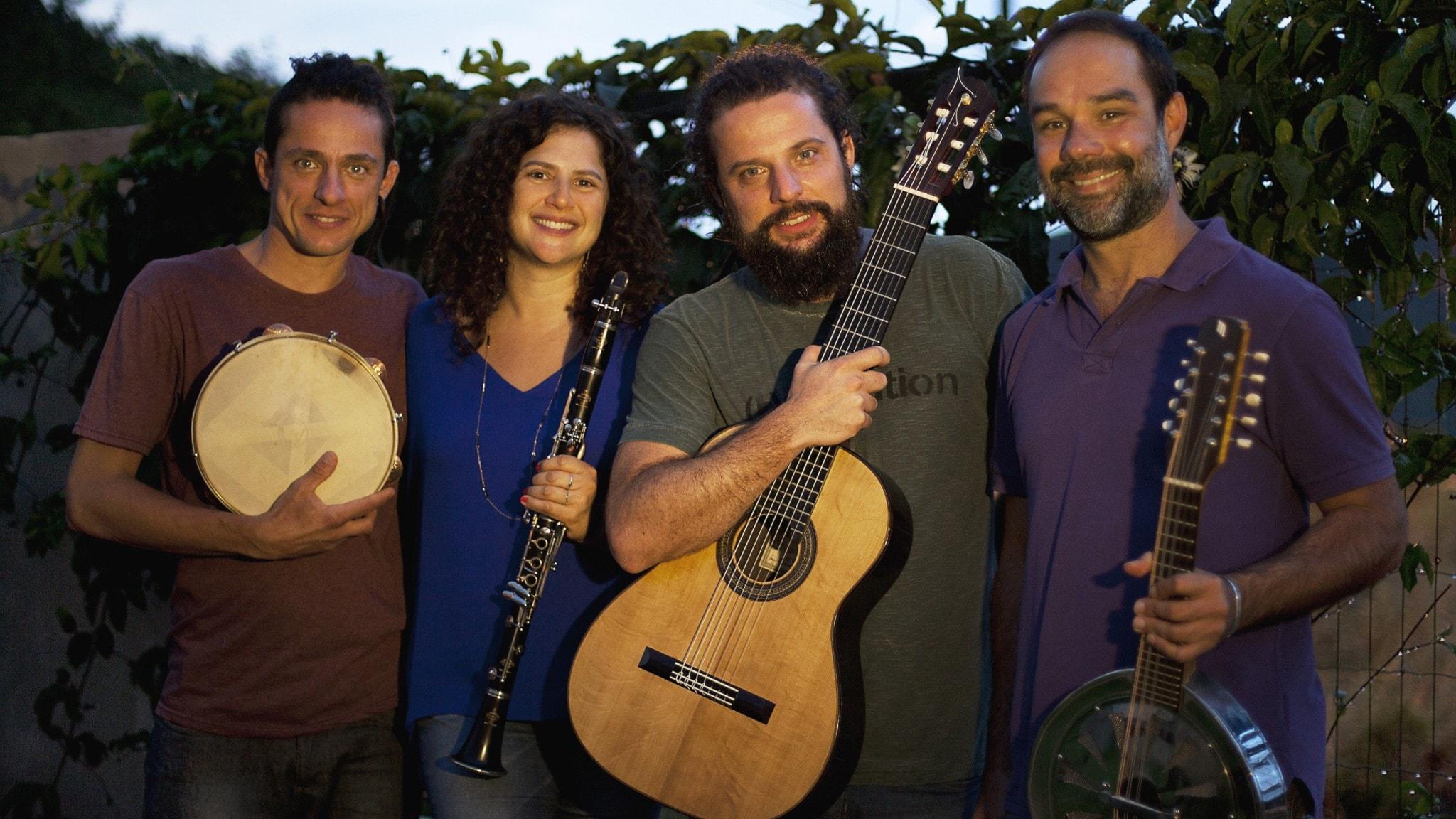 Tre män och en kvinna som ler in i kameran och har instrument i händerna.