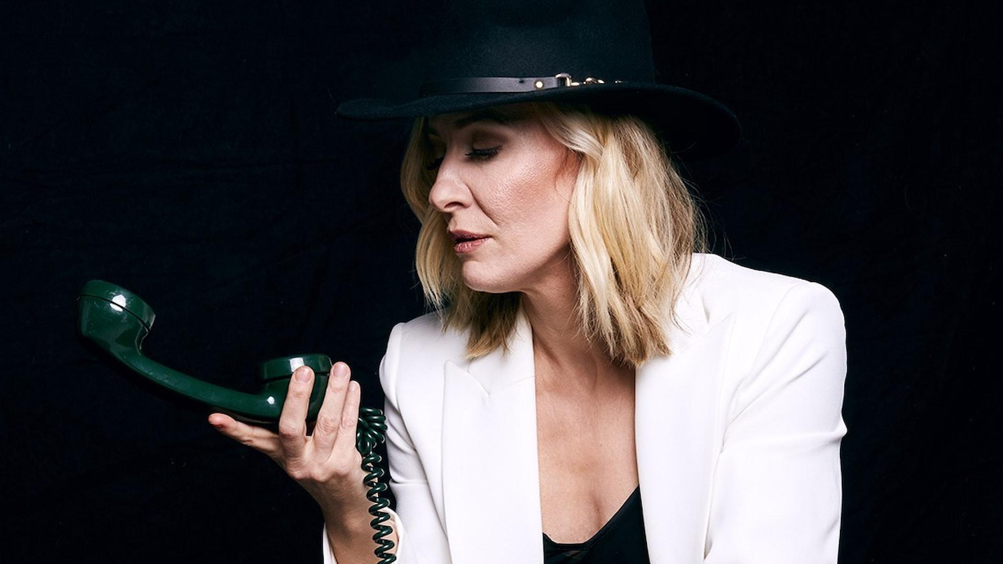 Sångerskan, pianisten och låtskrivaren Ida Sand sitter i vit kavaj med svart hatt mot en svart bakgrund och tittar på en telefonlur som hon har i handen. Foto: ACT_Josefine Bäckström