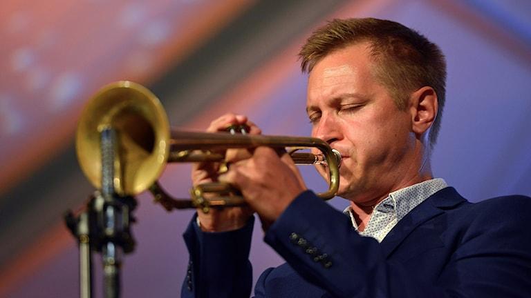 Trumpetaren Jukka Eskola som spelar i sin trumpet framför en mikrofon.