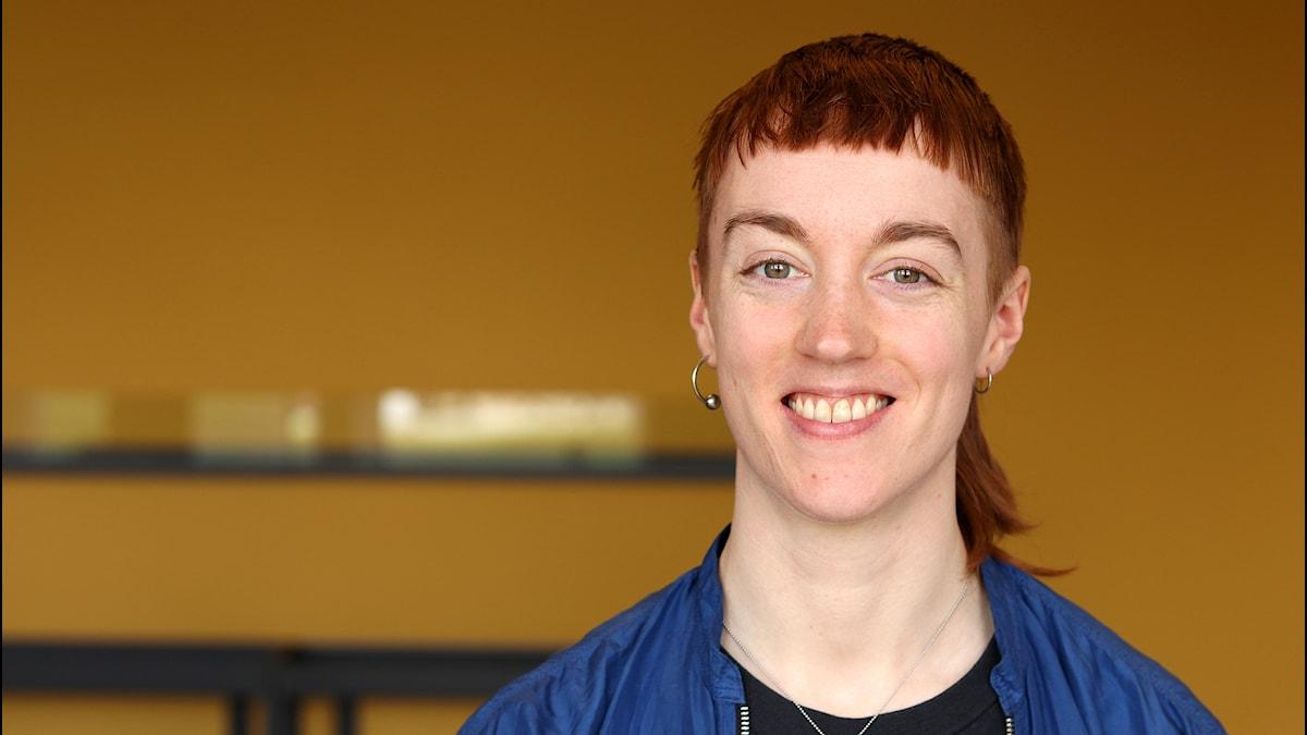 Porträtt av en kortklippt kvinna mot en gul bakgrund.