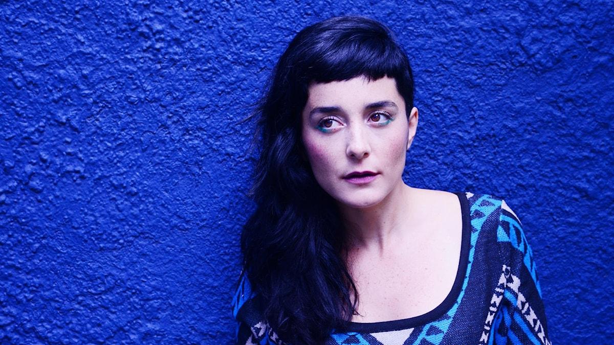 Porträtt av en mörkhårig ung kvinna mot en blå vägg