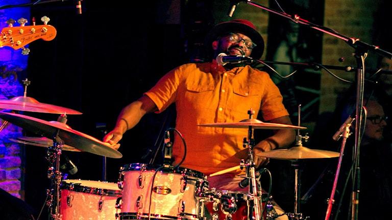Man i hatt som spelar trummor med stor inlevelse