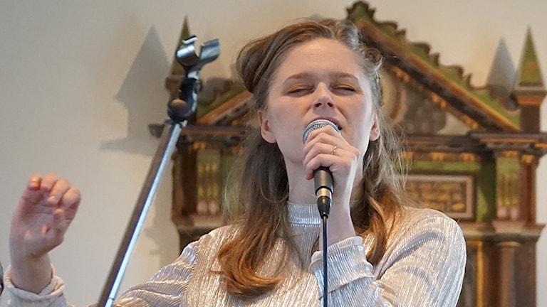 Sångerska som sjunger i mikrofon