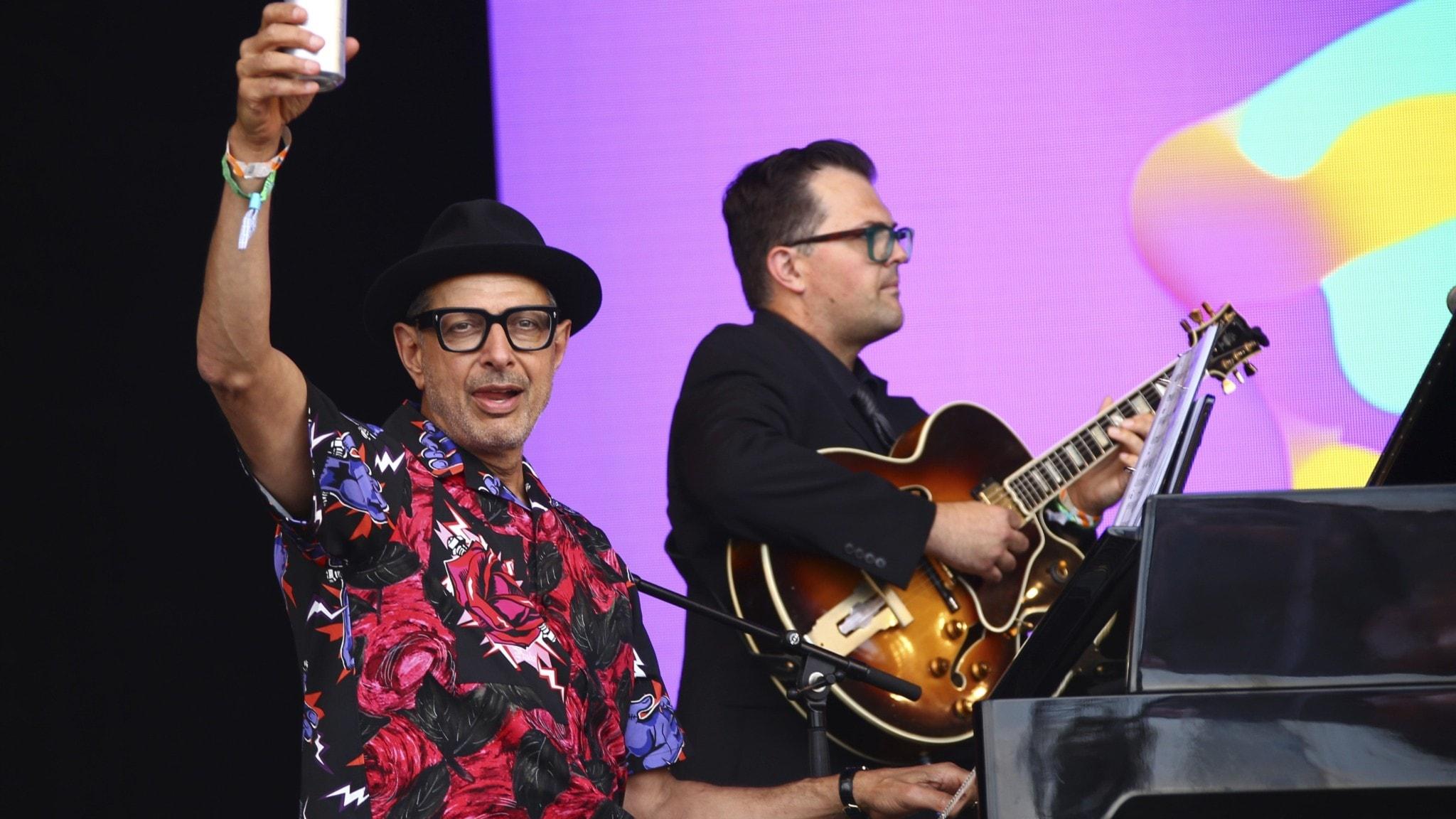 Skådespelaren och pianisten Jeff Goldblum sitter bakom flygeln och höjer en aluminiumburk mot publiken. I bakgrunden en gitarrist.
