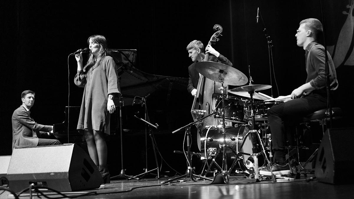 En sångerska, en pianist, en basist och en trumslagare under en konsert
