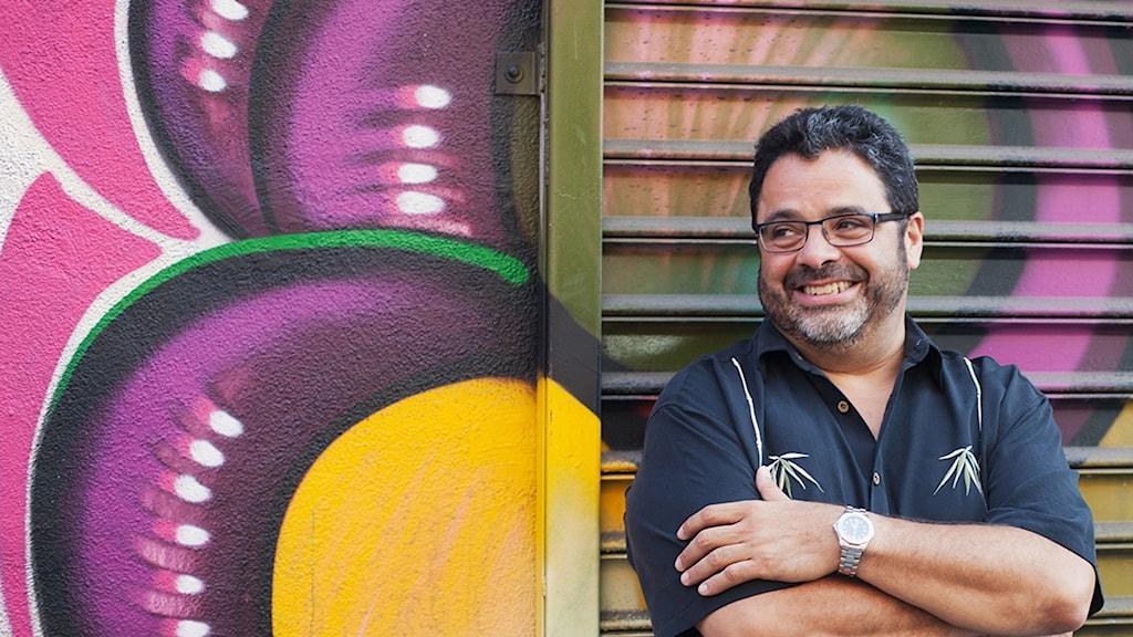 Glad man framför färgglad graffitivägg