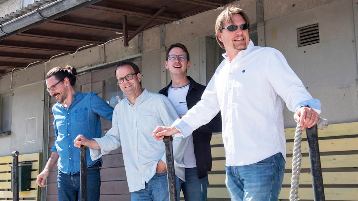 Fyra män i solskenet på en lastbrygga