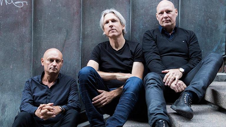 Tre män som sitter i en trappa