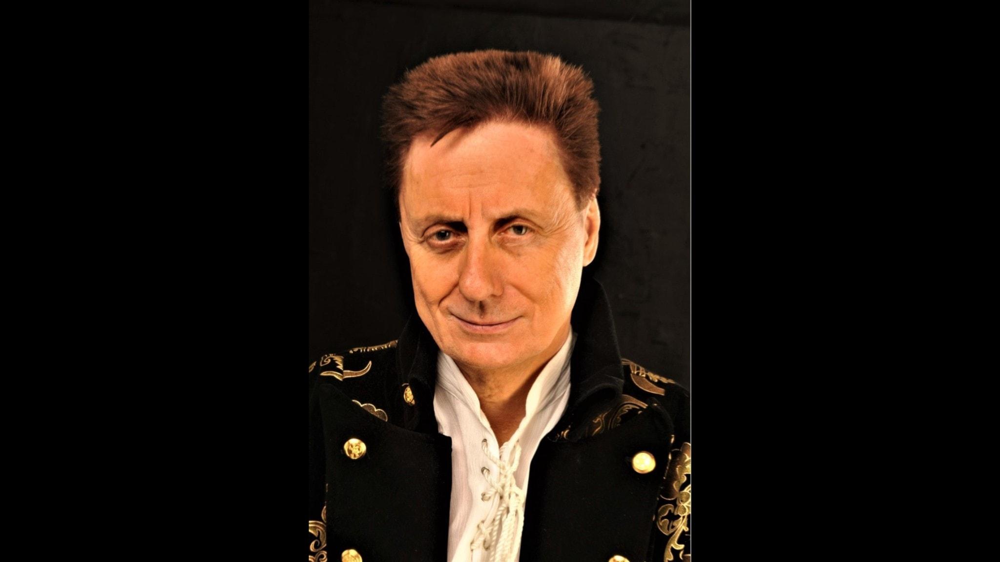 Hans Edler ler och tittar in i kameran. Han är klädd i en svart jacka, med gulddekorationer.