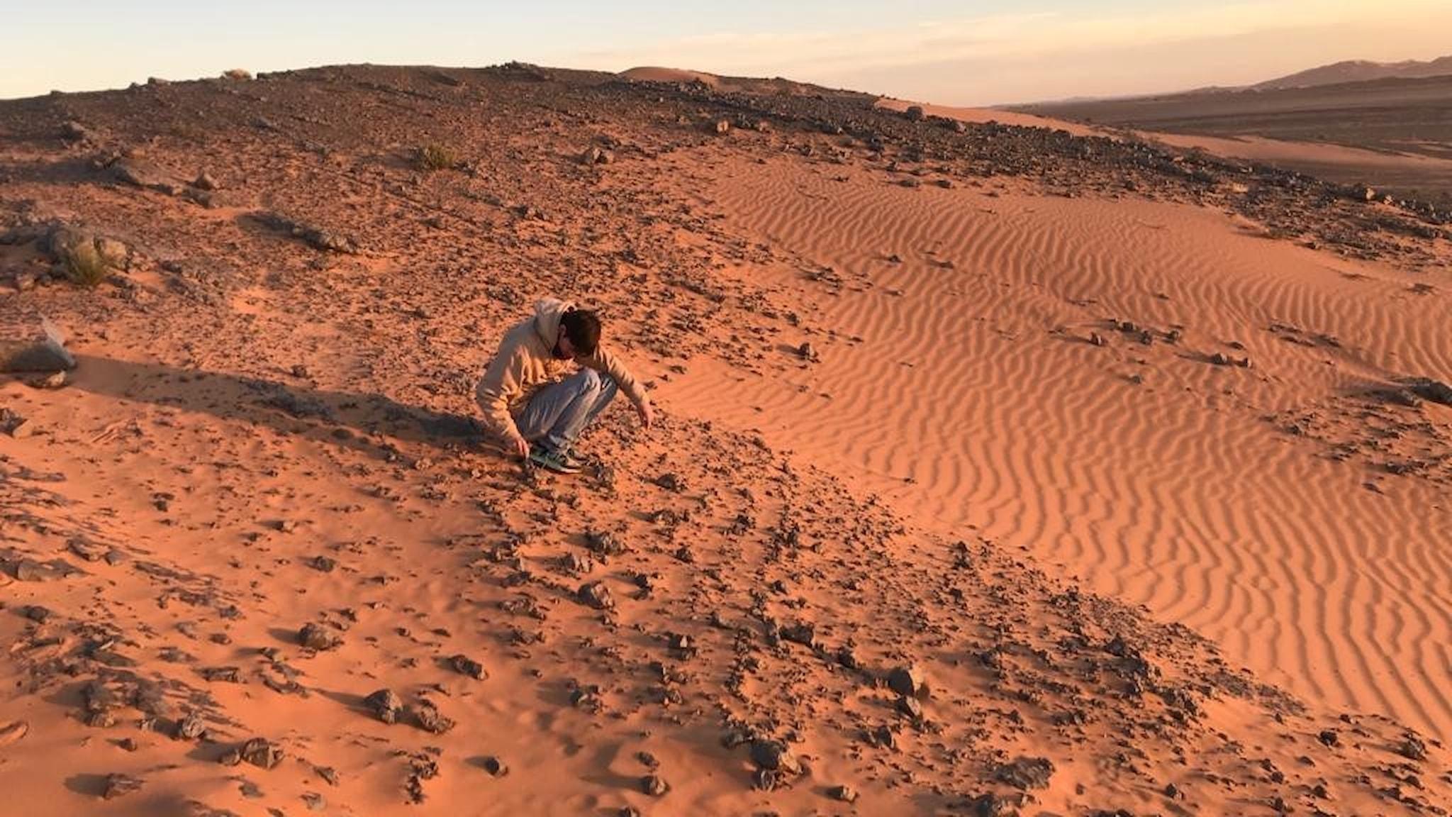 Ola Keijer sitter på huk i öknen - sanden är röd och formad som vågor efter att det blåst i den.