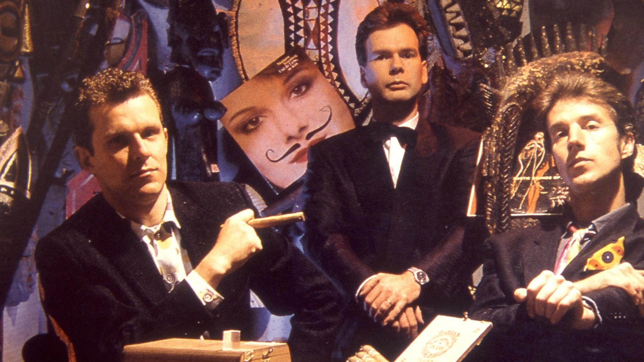 Tyska trion Der Plan har smoking och fluga. De röker cigarr och ser ut att vara på en klubb med många bilder på väggarna.