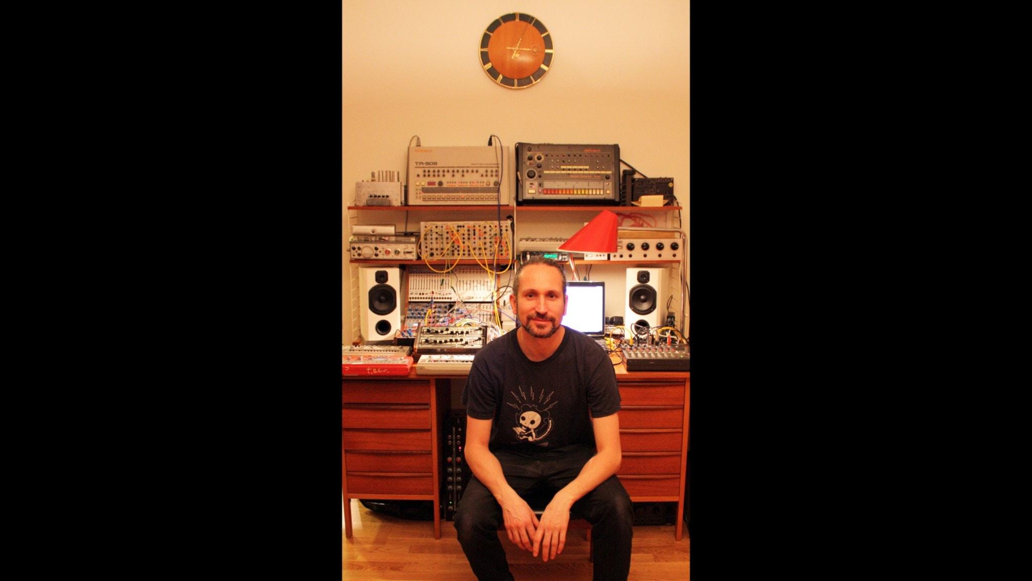 Daniel Araya bär svart t-shirt med tryck. Han har skägg och bakåtstruket hår. Han sitter med ett leende framför sina syntar i studion.