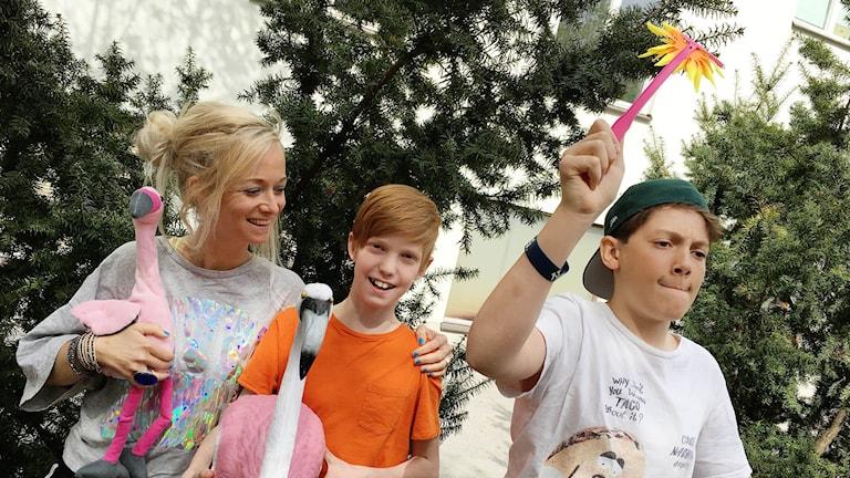 Amelie, Zacharias och Samson står framför ett par träd. Amelie och Zacharias håller i varsin flamingo i plast.