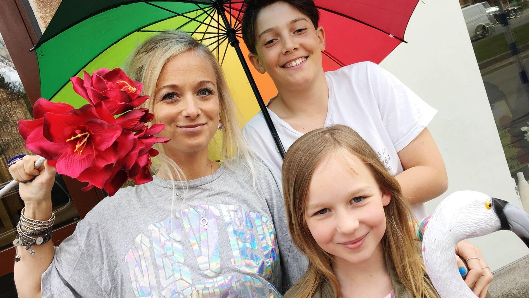 Amelie, Samson och Ella står under ett regnbågsfärgat paraply. Amelie har röda blommor i handen.