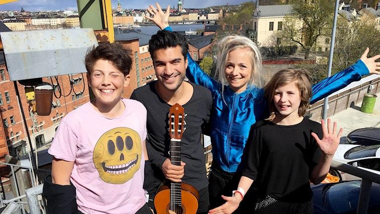 Samson, Farzad, Amelie och Liv står uppe på takterrassen. Farzad håller i en gitarr.