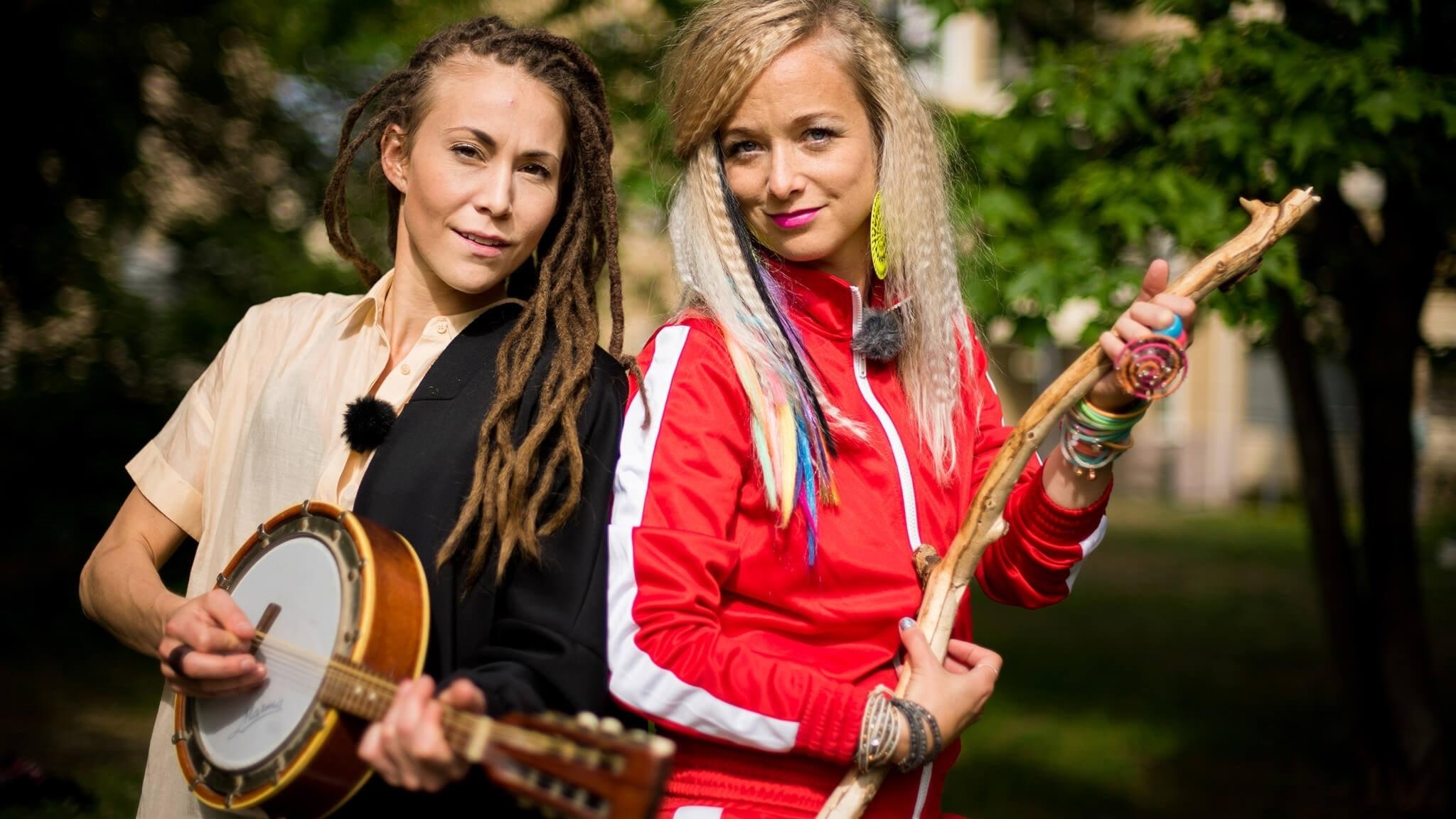 Mariette spelar på en mandolin, Amelie låtsas spela på en träpinne. De står ute i vildmarken.