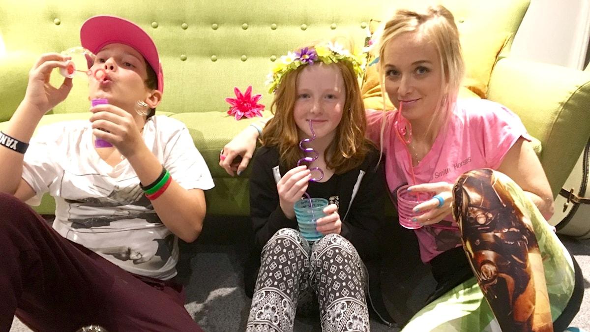 Samson Mirro, Ella Goddard och Amelie Nörgaard firar med saft och bubblor