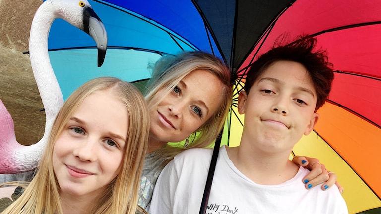 Lova, Amelie och Samson står under ett regnbågsfärgat paraply.
