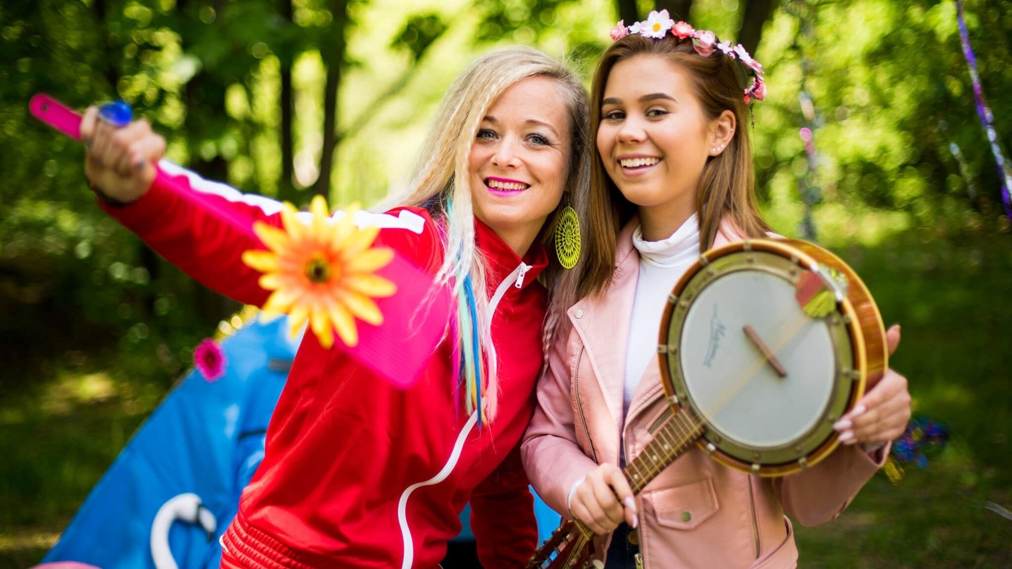 Amelie och Lisa Ajax står ute i skogen. Lisa Ajax håller i en mandolin.