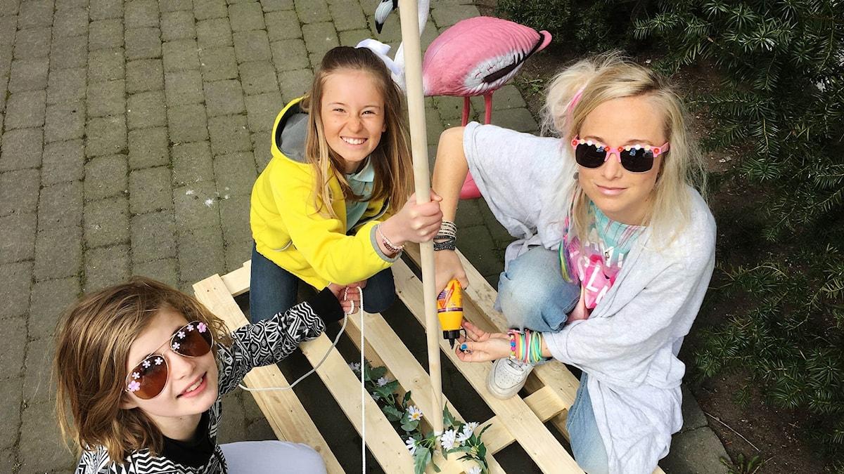 Liv, Julia och Amelie bygger på skräpflotten. I bakgrunden står en flamingo.