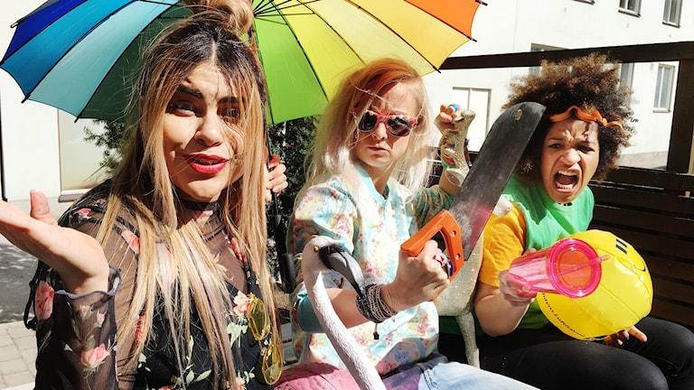 Arantxa, Amelie och Angelika sitter under ett paraply i solen. Amelie håller i en såg.