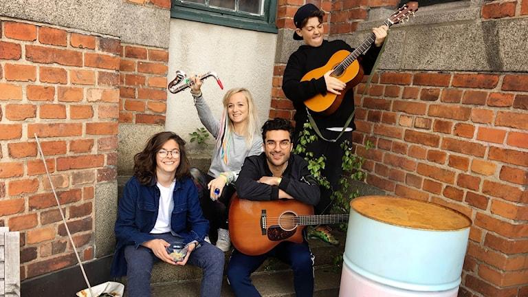 Bernard, Amelie, Farzad och Samson står och spelar olika instrument framför en tegelvägg uppe på takterrassen.