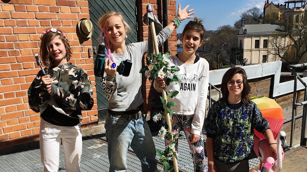 Liv, Amelie, Lois och Bernard står på skräpflotten och ler mot kameran. Flottens mast är täckt av blommor.