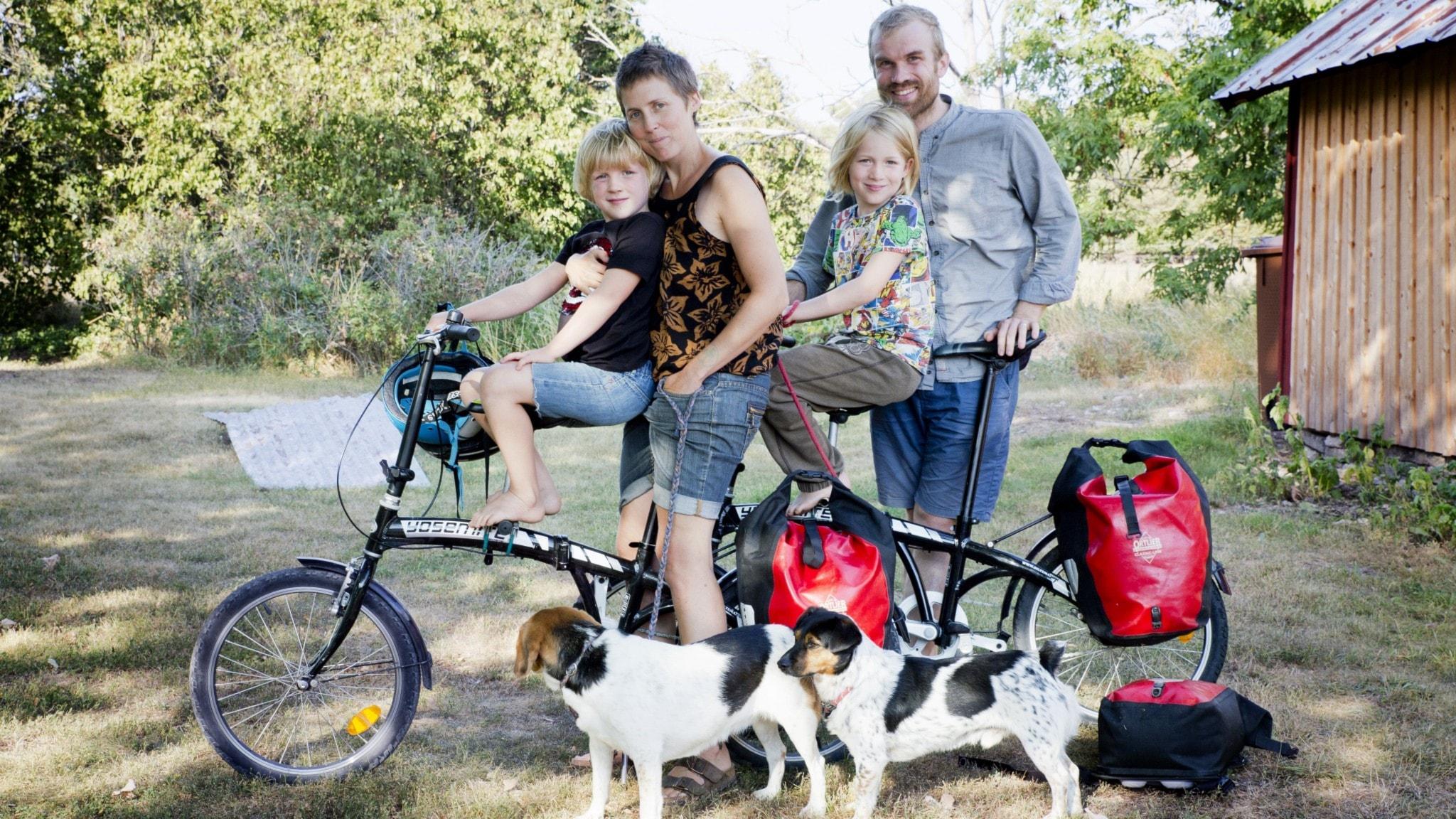 Familjen Ulbricht med cyklar och två hundar ute i trädgården.