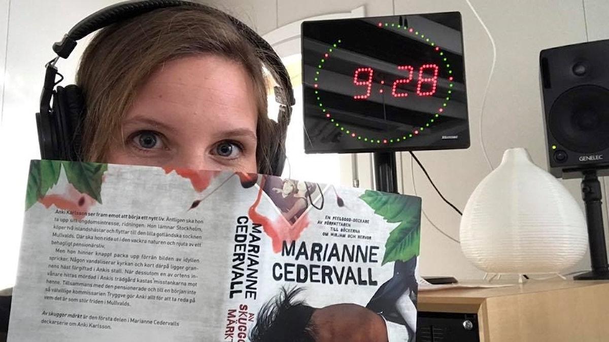 Amanda Heijbel med Marianne Cedervalls bok Av skuggor märkt.