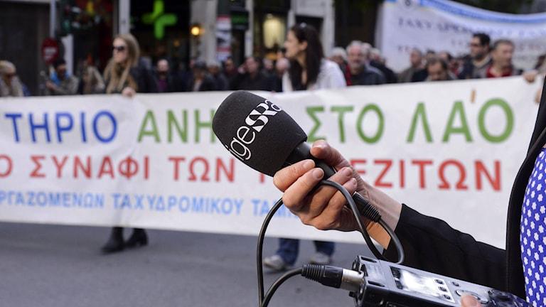 Mikrofon med Sveriges Radios loggotyp hålls upp framför demonstrationer med grekiska banderoller. Foto: Mikolas Kominis/Sveriges Radio.