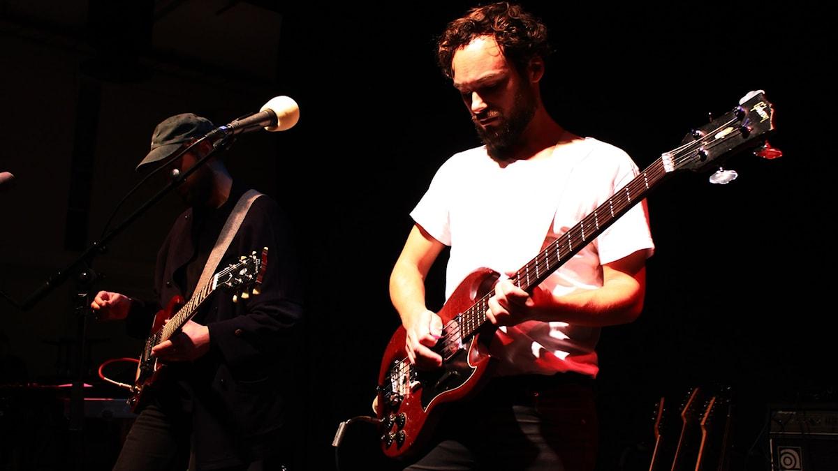 This is Head står och spelar gitarr plus bas. Sångaren är kraftigt upplyst i vit tröja. Foto: Gustaf Widegård/SR