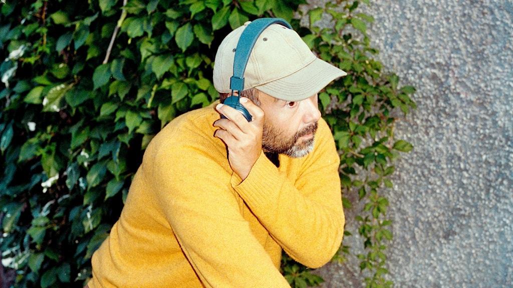 En person med gul tröja och beige keps cyklar. På huvudet har han ett par hörlurar där han lyssnar på P3.