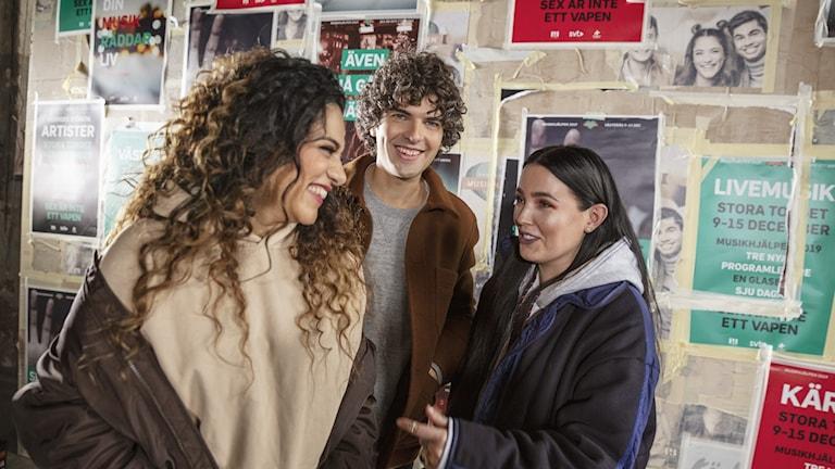 Farah Abadi, Daniel Hallberg och Miriam Bryant står framför en affischerad vägg med Musikhjälpen-budskap. På bilden ser man att Miriam precis har sagt något och alla tre fnissar.