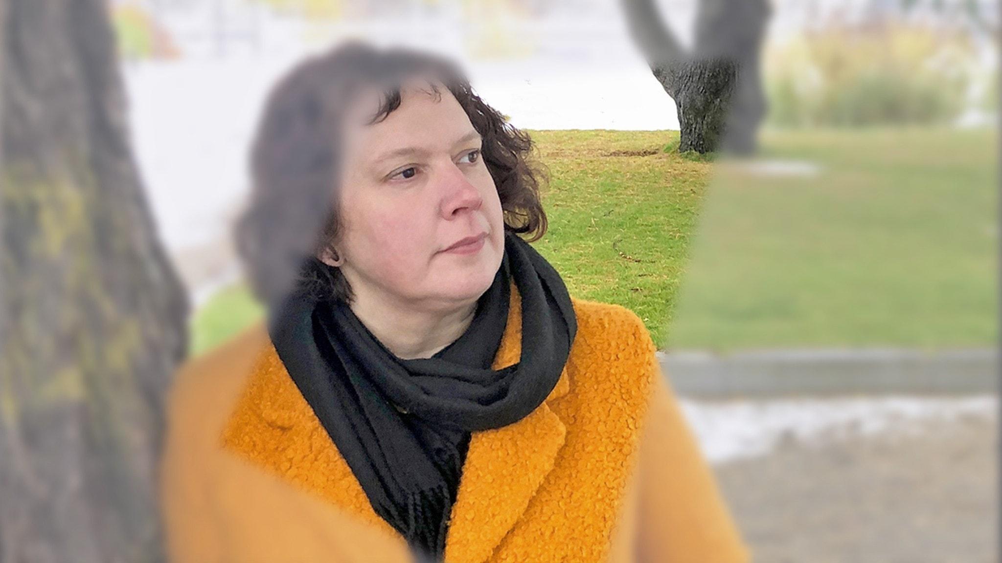 Anna-Mia Johansson i gul kappa vid ett träd