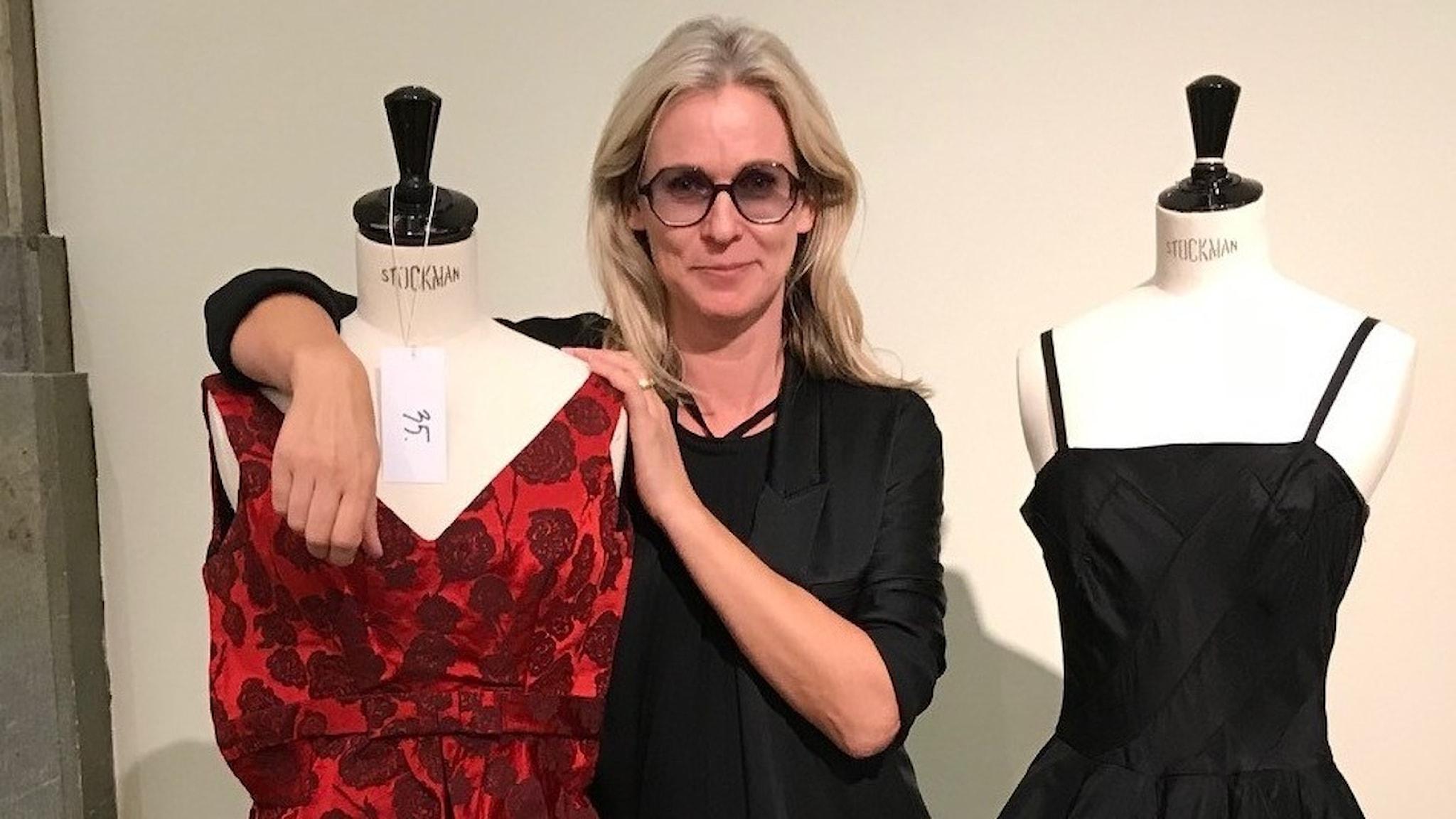 Susanna Strömquist i svart klänning tittar leende in i kameran. På vardera sidan om henne står en provdocka med en klänning på, en är röd, en är svart. Det är festklänningar från skrädderiet NKs franska damskrädderi.