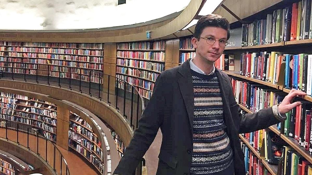 Karl Berglund vid hylla med böcker