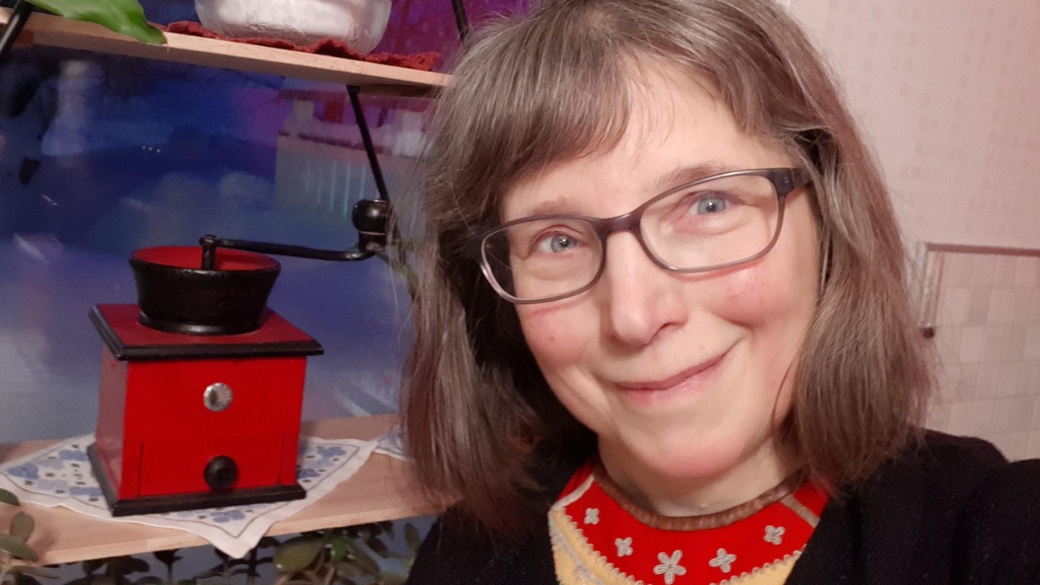 Lena Maria Nilsson med en kaffekvarn i bakgrunden
